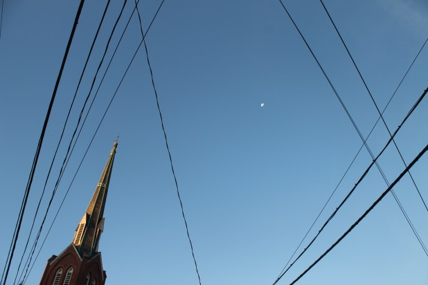 Juxtaposition of cables, wires, church steeple, and moon in the morning sky